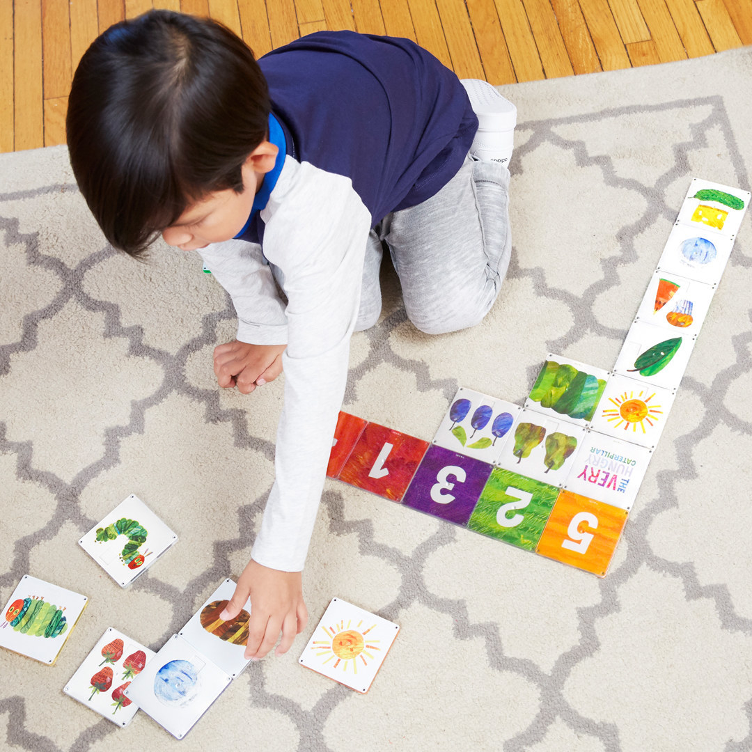 A small model kneeling on the floor and playing with a set of square tiles that have illustrations of animals and numbers on them