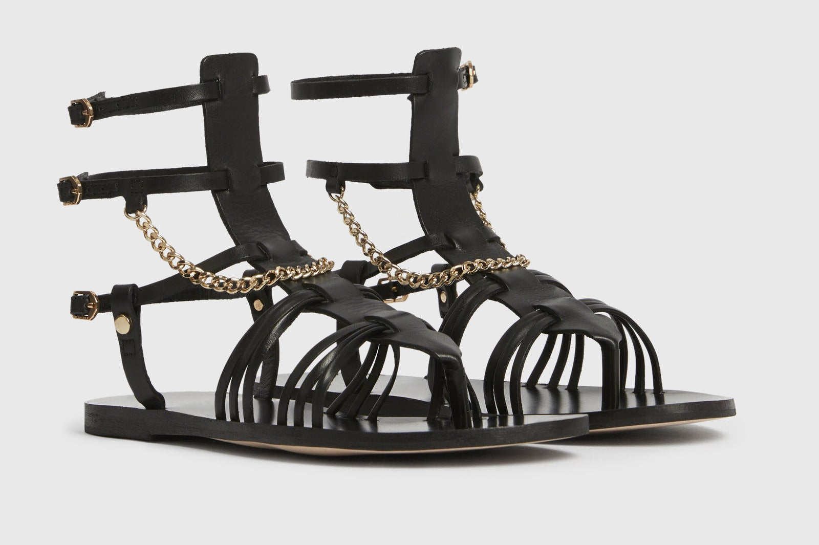 black gladiator style sandals with a gold tone chain as an accent and two straps that go right at the ankles