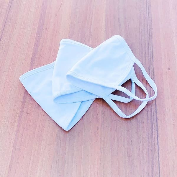 Three plain white face masks with loops that go around the ears sitting on a table