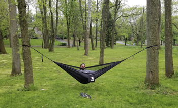 a reviewer in the black hammock between two trees