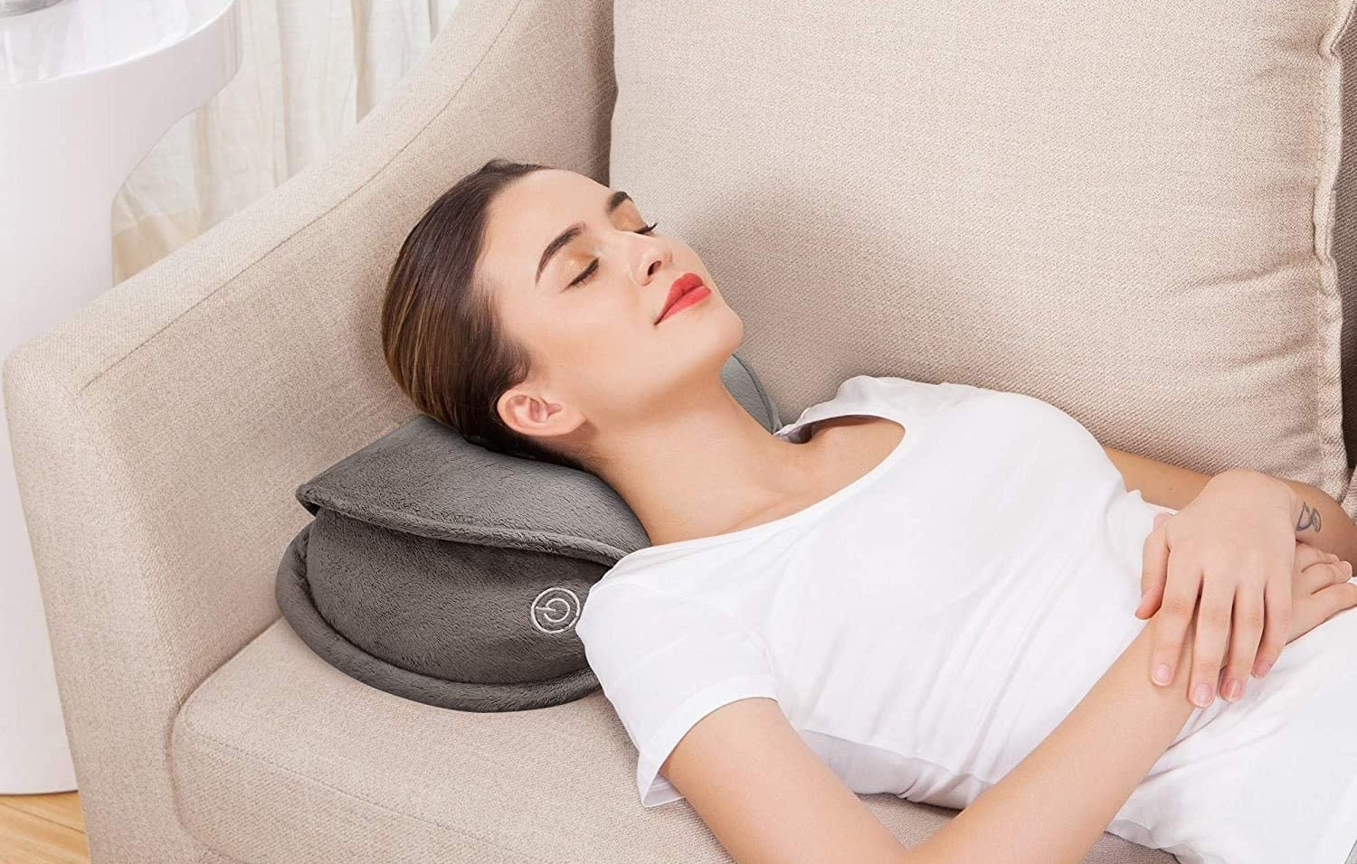 A person lying on a couch using the massage pillow