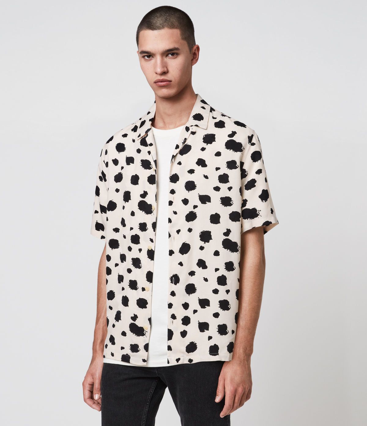model wearing a button down short sleeve dress in a dalmatian print