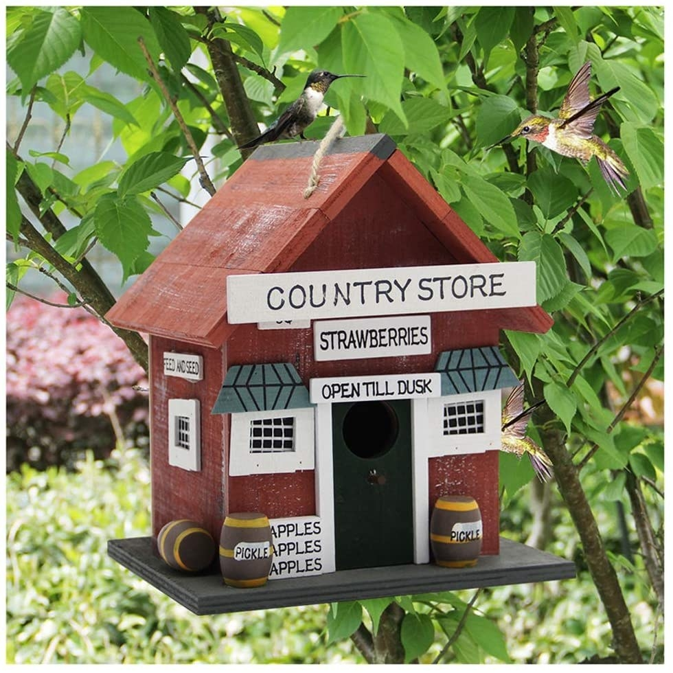 "the red birdhouse with a sign that says ""country store"" on it"