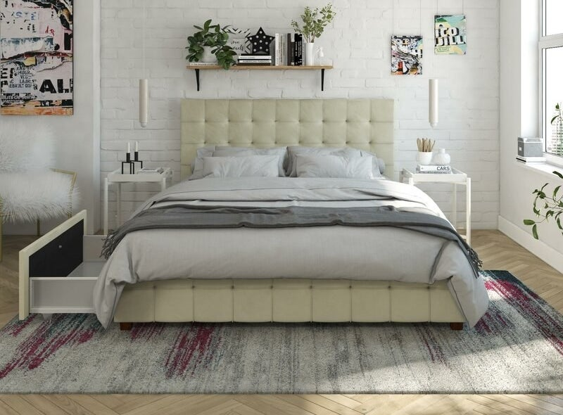 A ivory-velvet color bed frame with a large drawer opening on one side