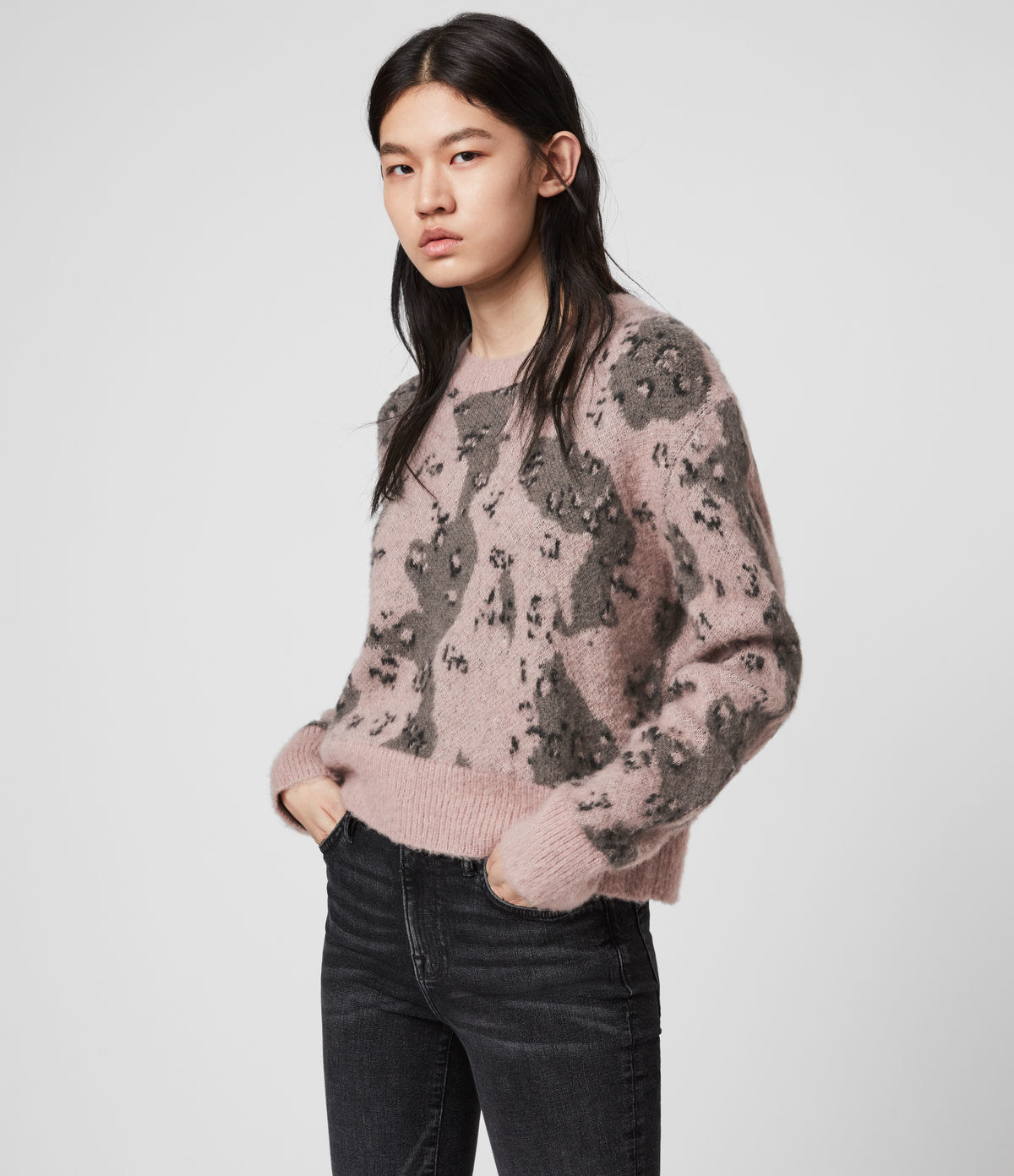 model wearing light pink crewneck sweater with gray and black abstract camo print