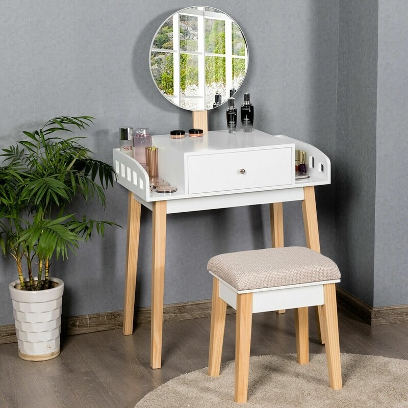 A white vanity and chair with wooden legs, a circular mirror, and cushion top chair