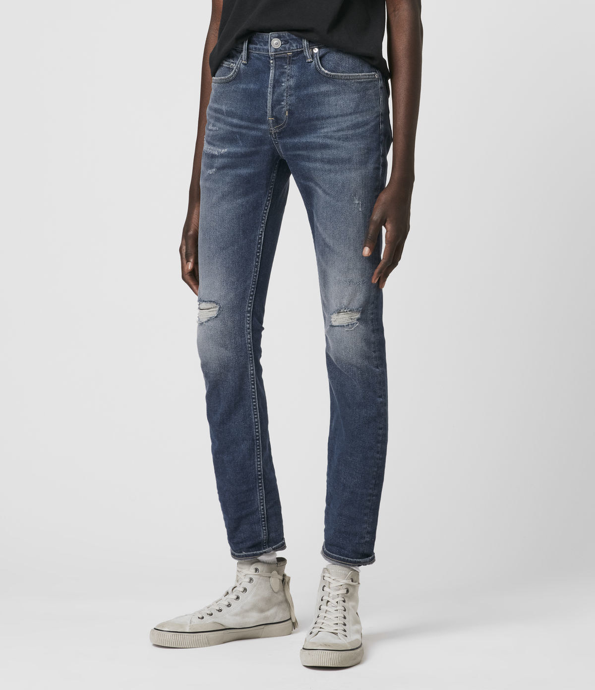 model wearing skinny medium wash jeans with whiskering and rips above the knees with high-top sneakers