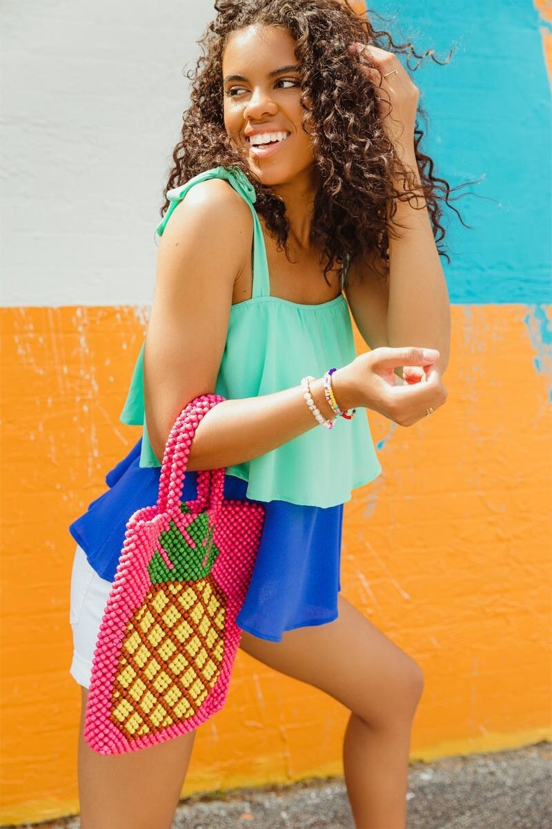 A model carrying the bag, which is made entirely out of beads and is hot pink with a yellow and green pineapple on it