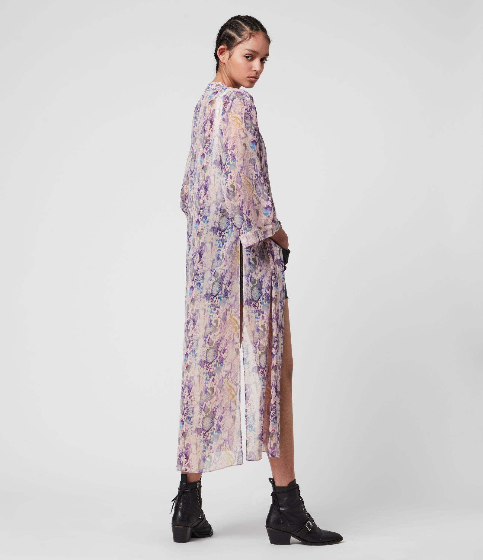 model with back facing the camera wearing a light pink and purple snakeskin print kimono that has a side slit to the waist and an ankle length
