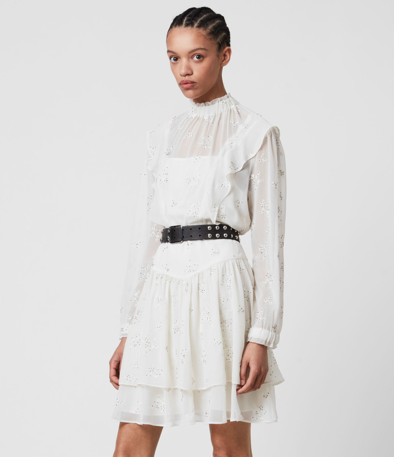 model wearing white long sleeve eyelet mini dress with gathered high neck, ruffles at chest, ruffles at hem with a Victorian style
