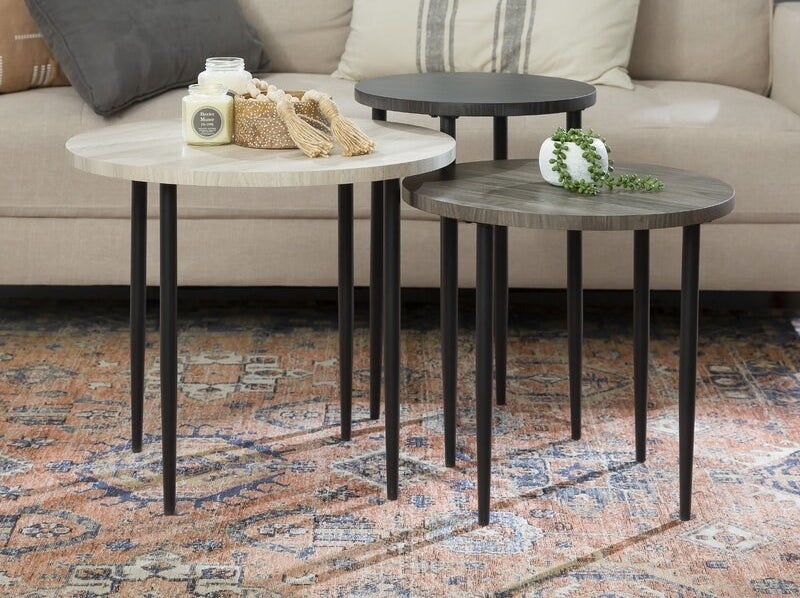 Three small oval-top tables with black legs