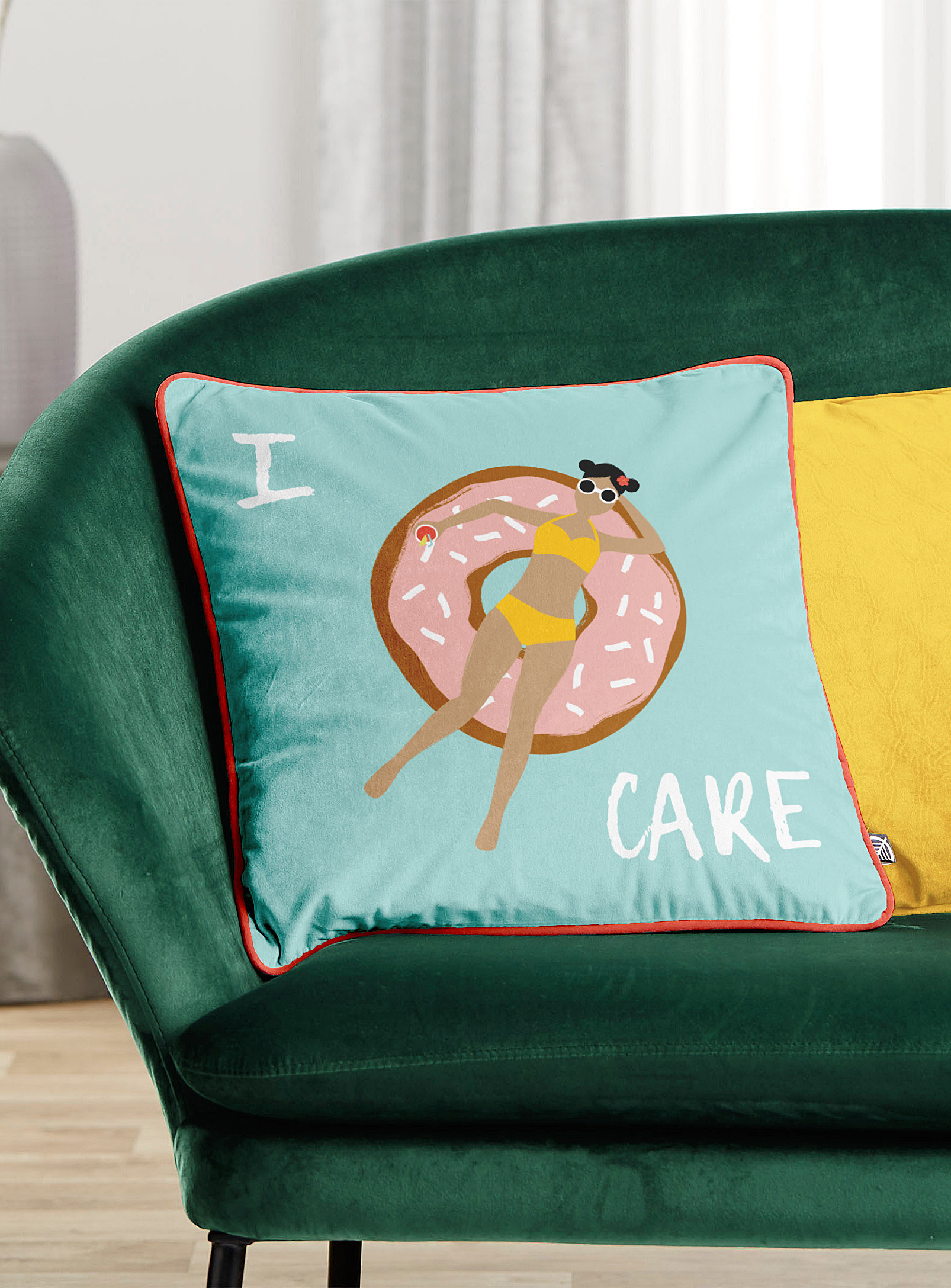 A cushion with the print of a person swimming on a donut floatie