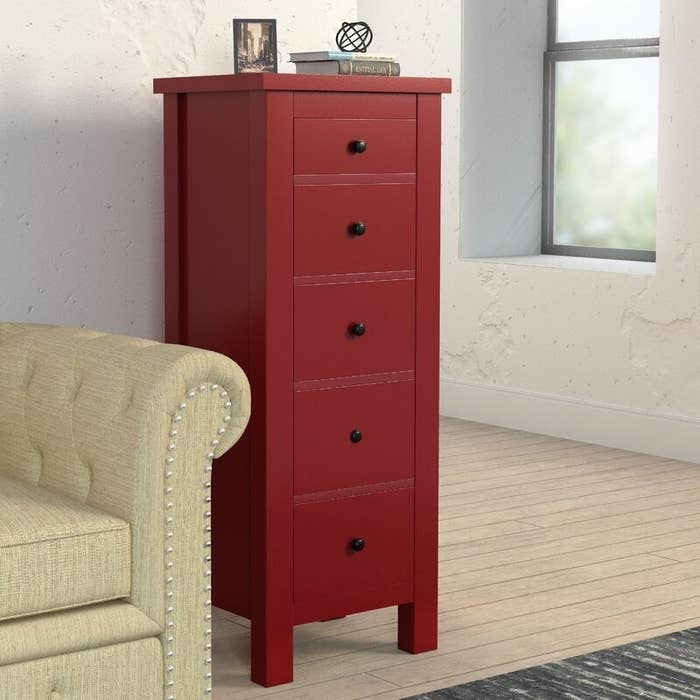 A deep red five-drawer chest with round black knobs