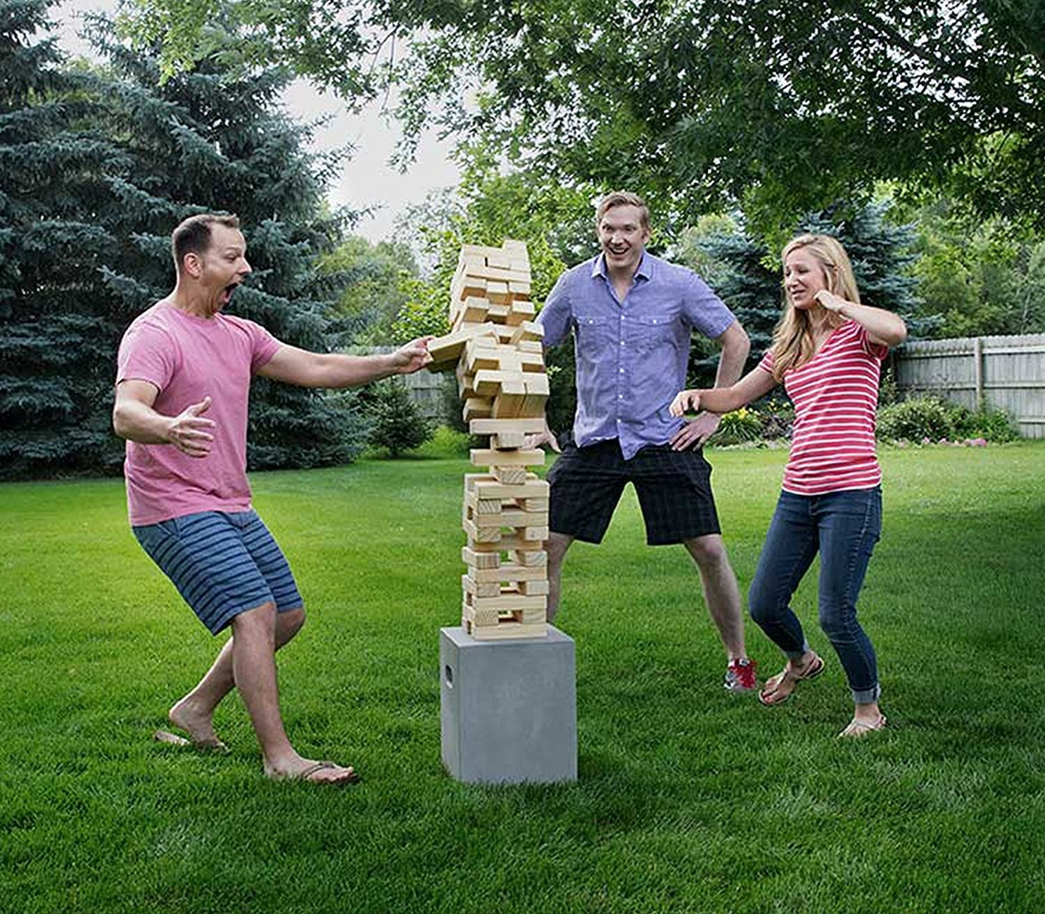 three models playing with the stackable tower of blocks