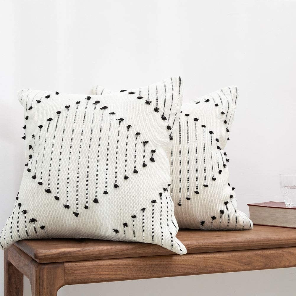 a pair of white pillows with black diamond designs on them