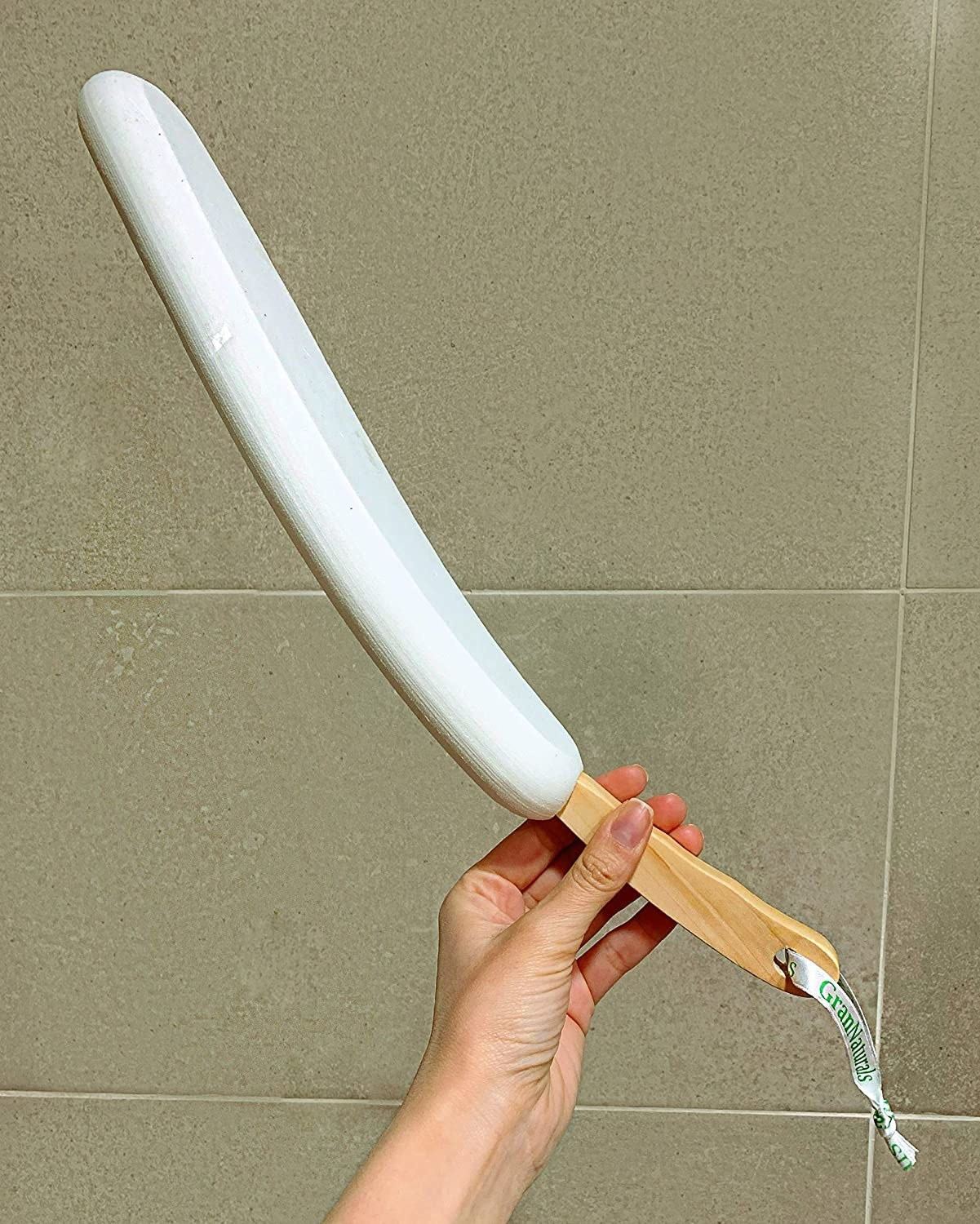 A person holds up the long curved lotion applicator