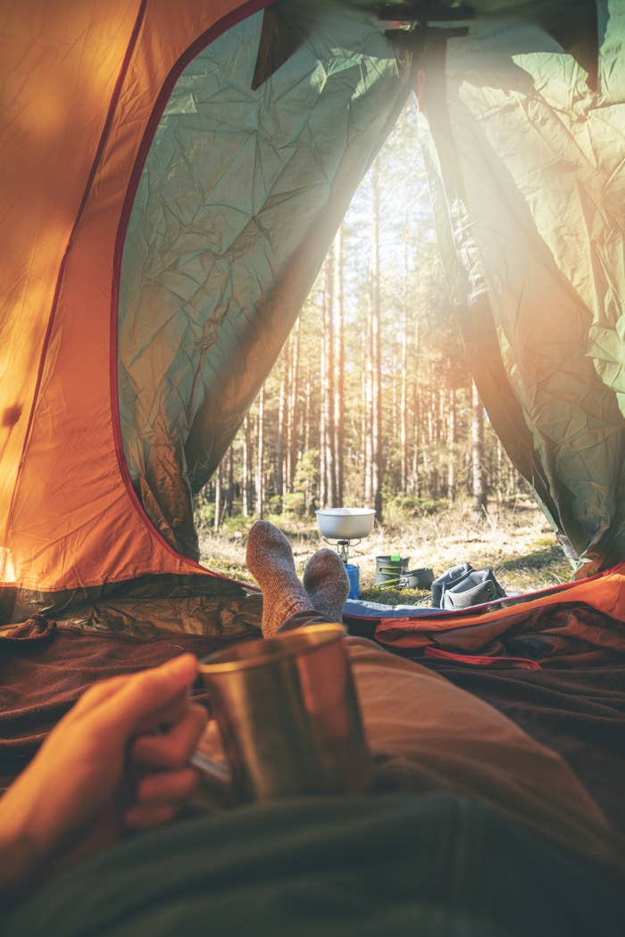 Man relaxing in tent after hike with cup of tea