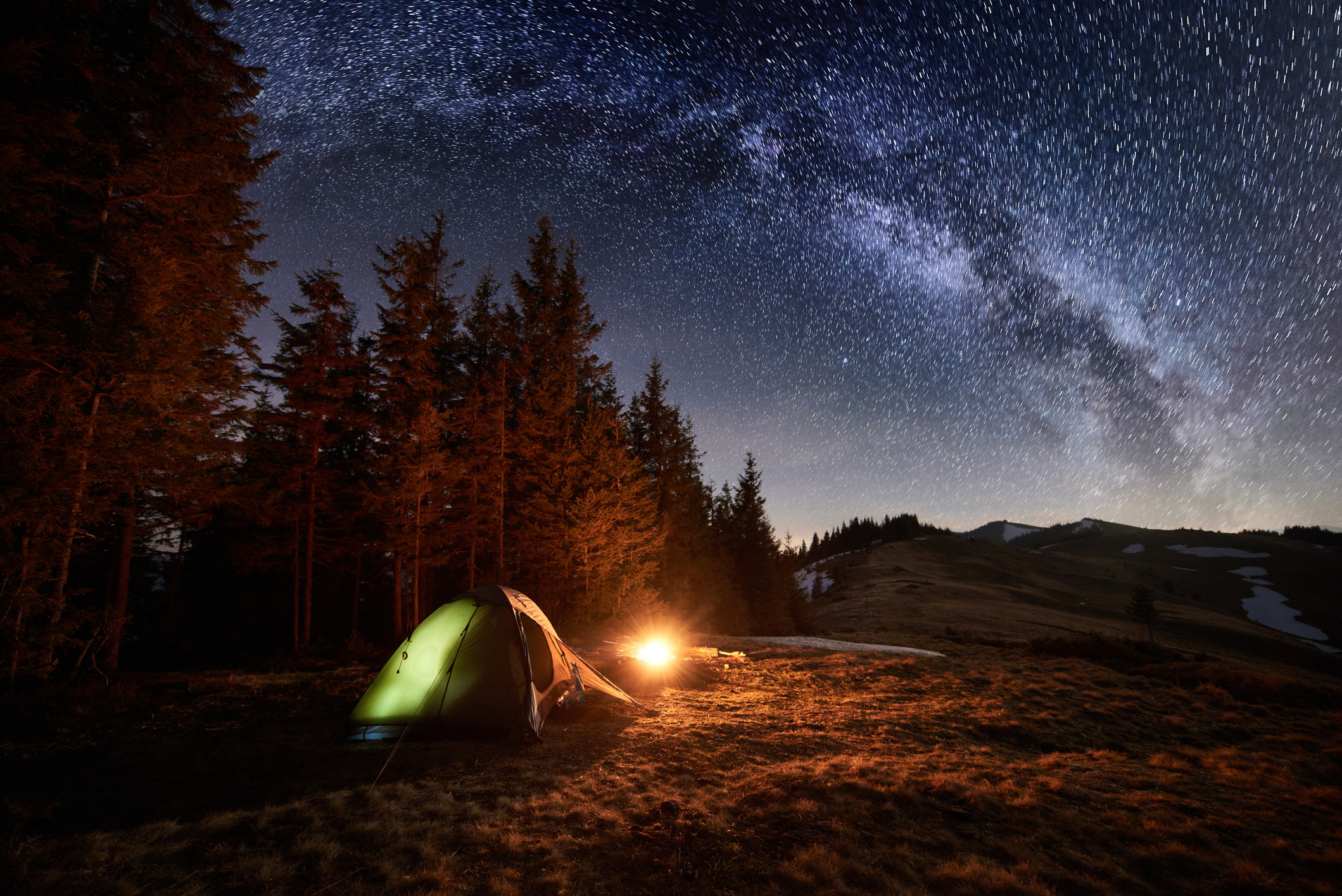 Illuminated tent under a starry night sky