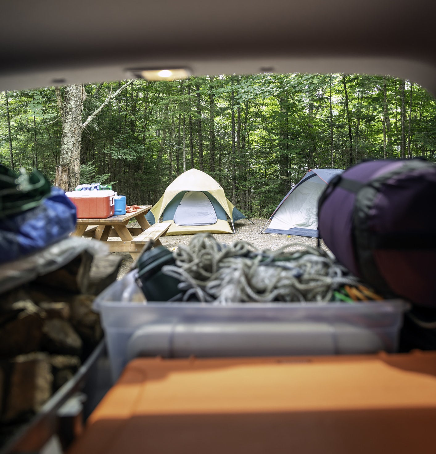 A car trunk full of camping gear with a tent in the background