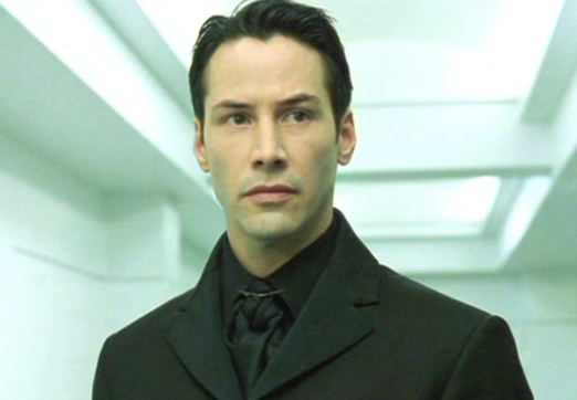 Keanu Reeves in The Matrix staring to the side of the room
