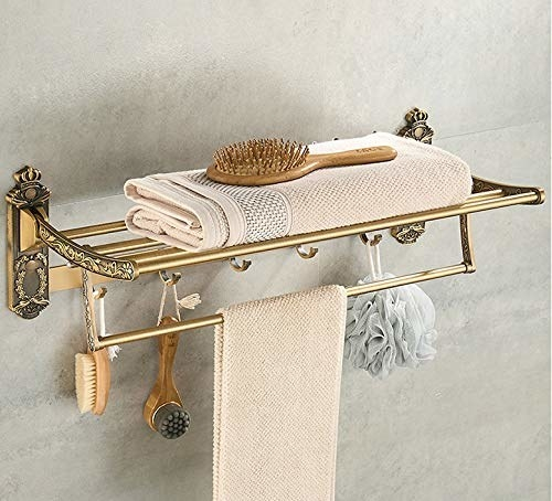 Golden towel rack with some towels, brushes and loofahs on it.