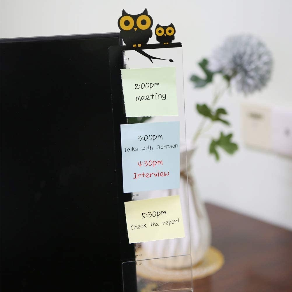 An acrylic memo board attached to the side of a computer with sticky notes on it