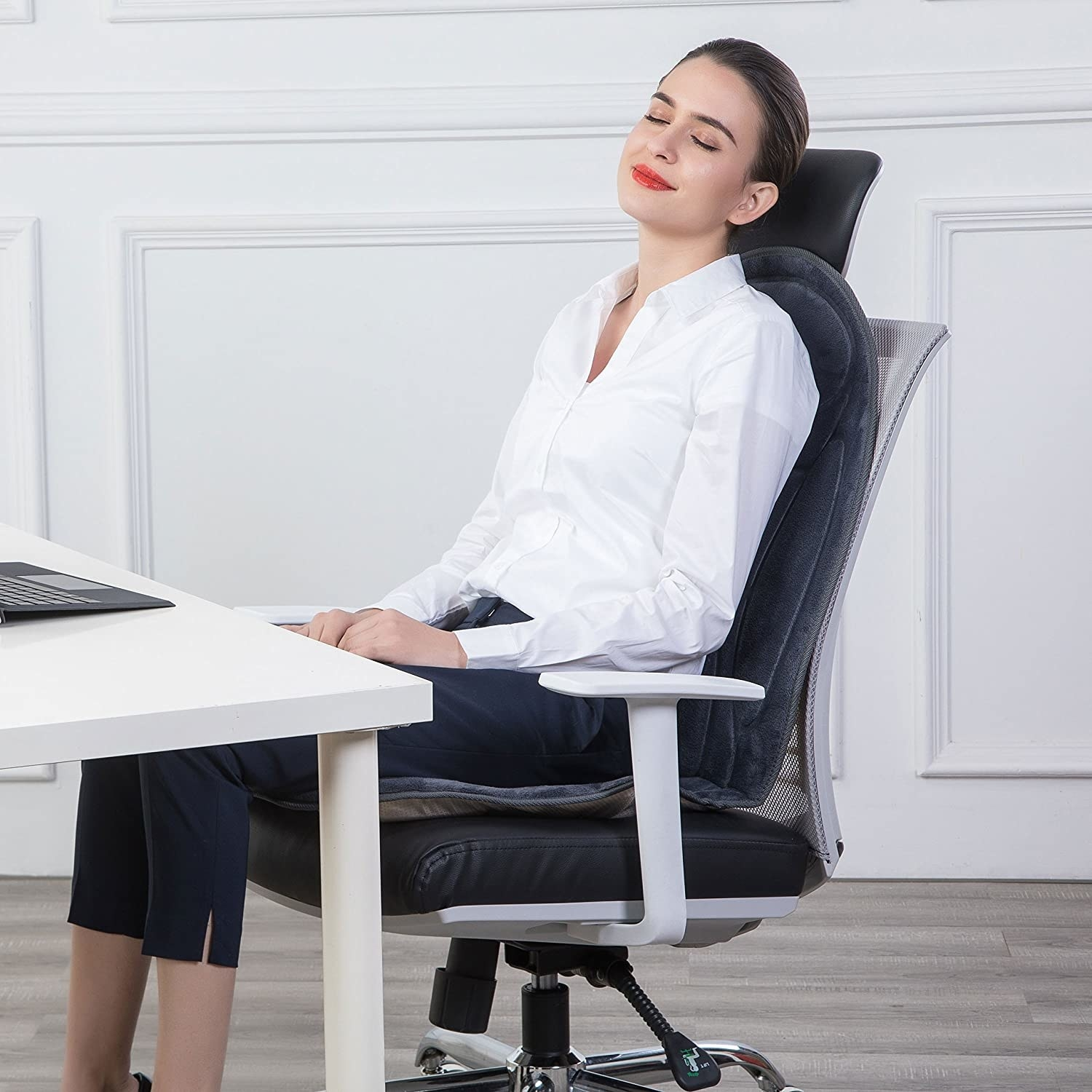 A person relaxing in their computer chair while using the massage seat cushion