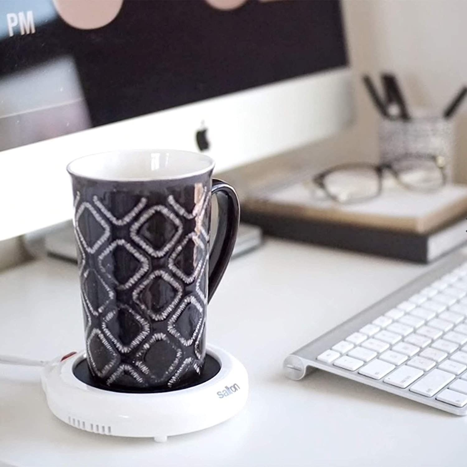 An electric mug warmer with a patterned mug on top of it