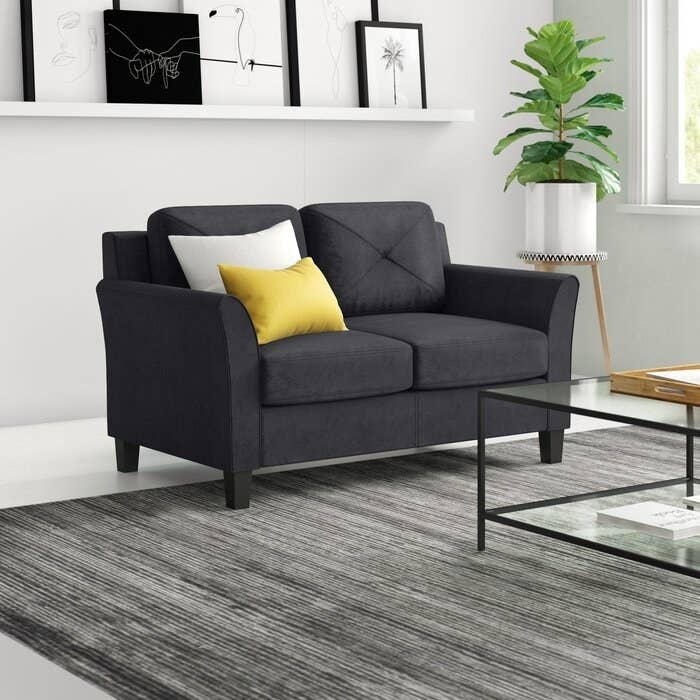 Loveseat in black in black upholstery with wooden legs and a slightly tapered arms