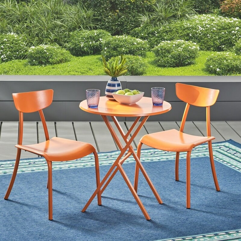 A bright orange metal set of two chairs and one round table with thin legs