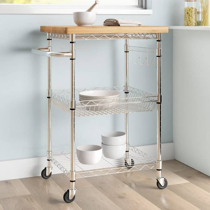 A metal frame kitchen cart on four caster wheels with two shelves and a wooden top