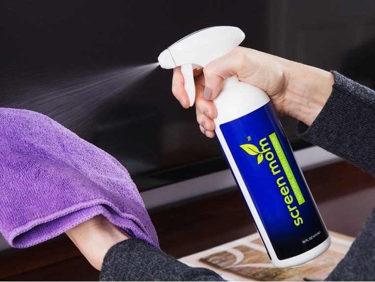 Hands spraying the product on the purple microfiber cloth