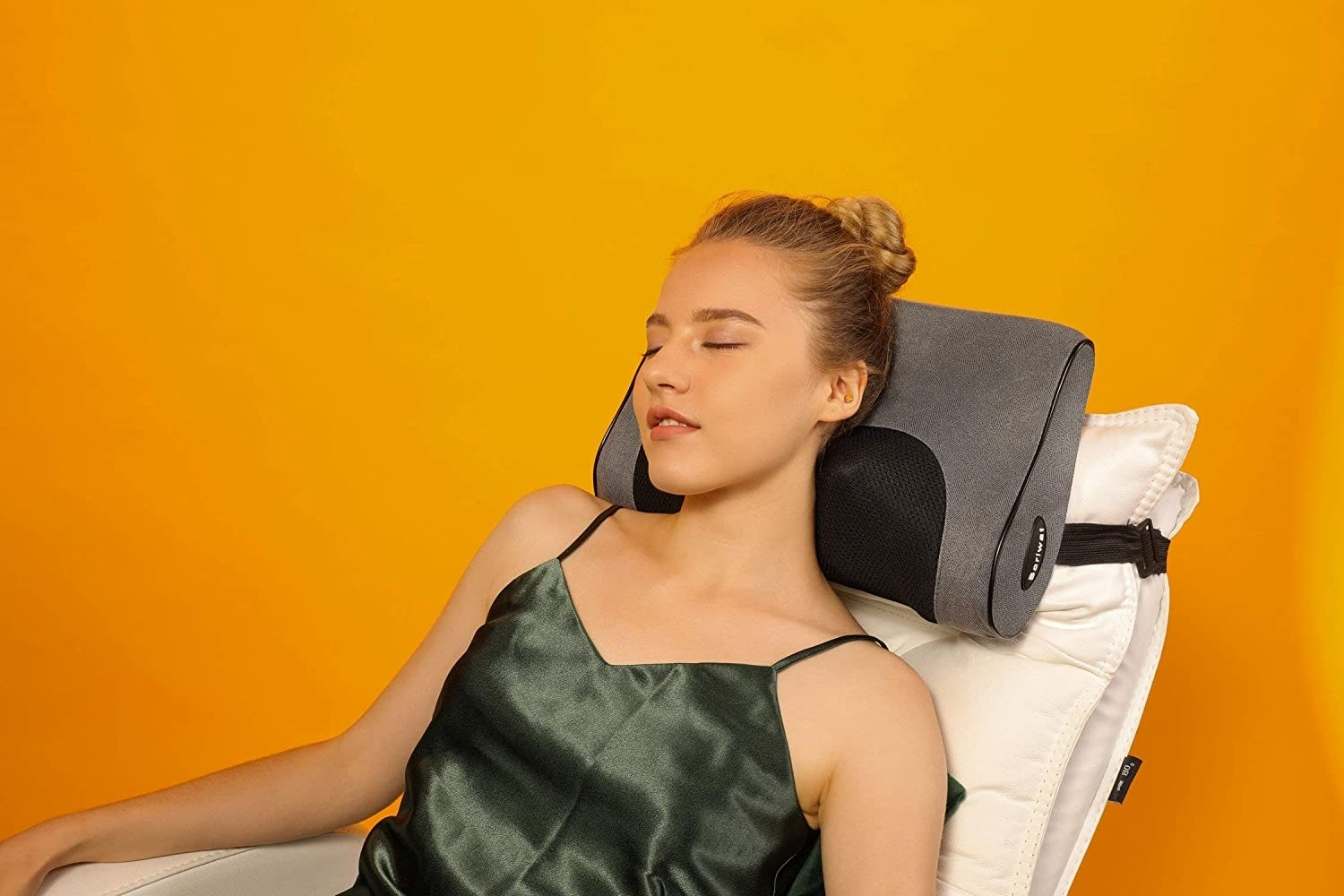 A person sitting in a chair with the massager attached to the headrest. It is massaging their shoulders while their head rests on the soft pillow top.