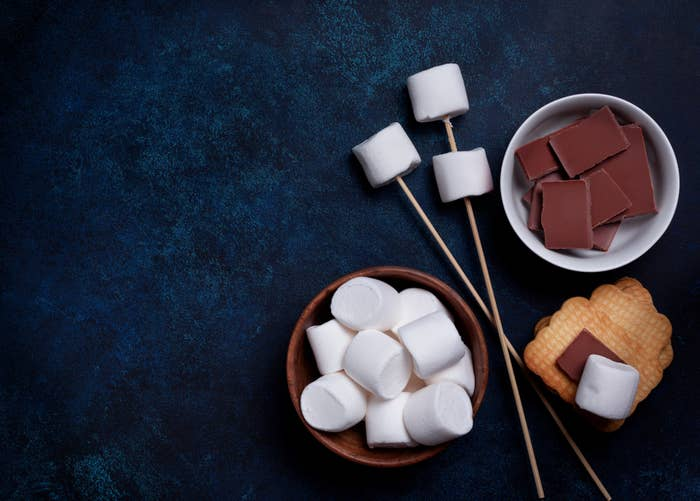 S'mores ingredients including marshmallows, chocolate, graham crackers, and skewers.