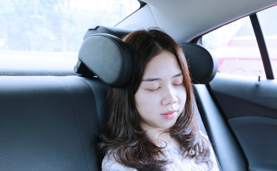 A person sleeping in the car with two headrest bumpers on either side of their head