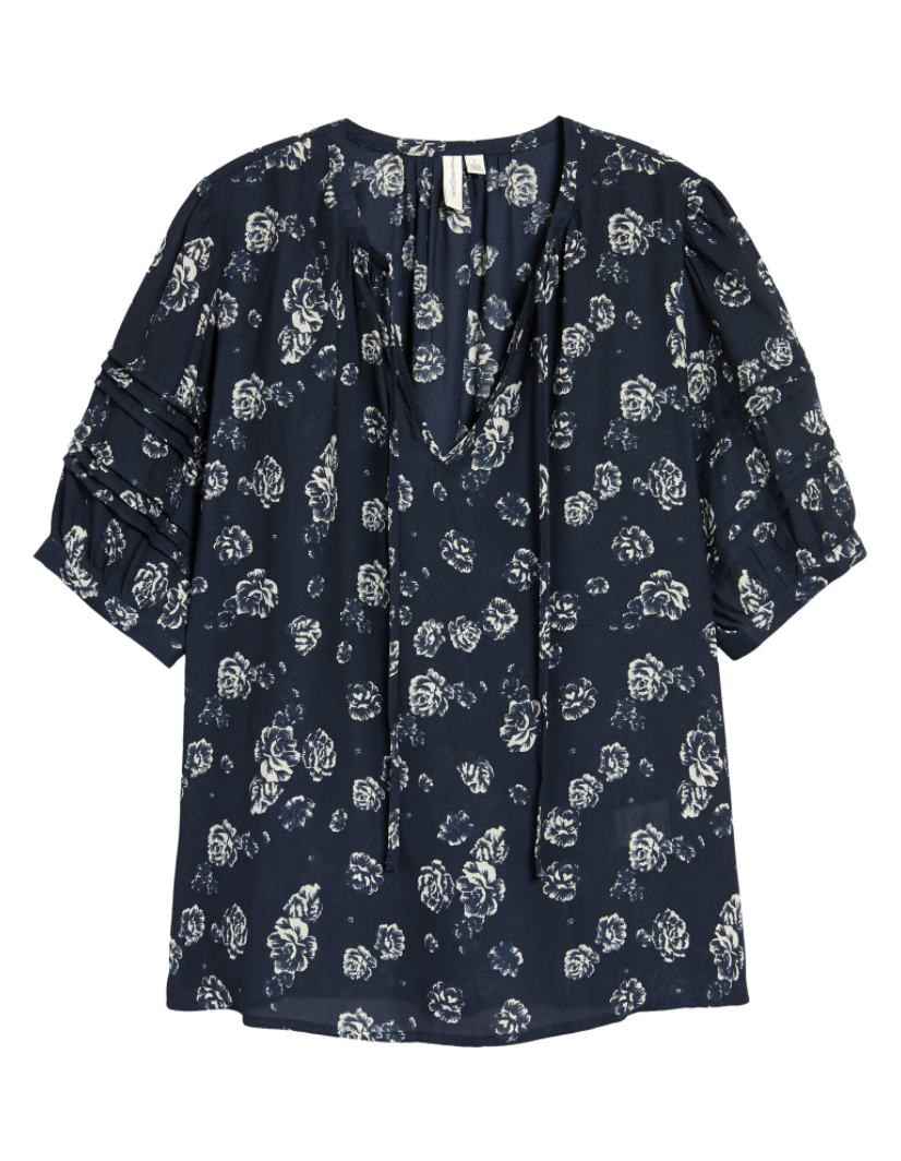 The puff-sleeve blouse with a split neck with ties in dark blue with white flowers all over