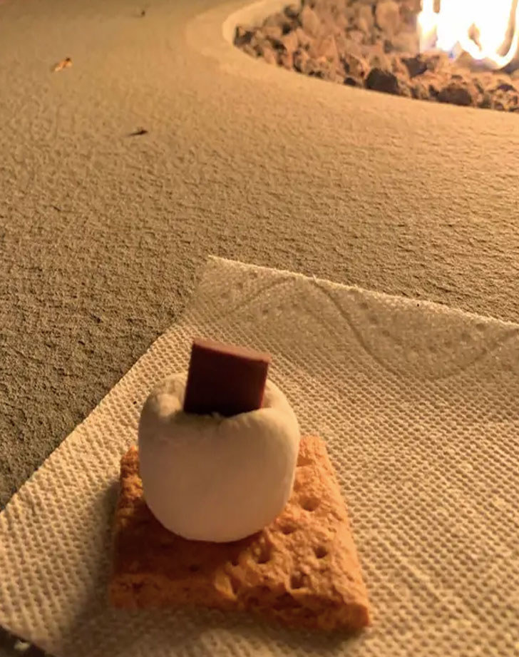 A chocolate square inside a marshmallow on top of a graham cracker.