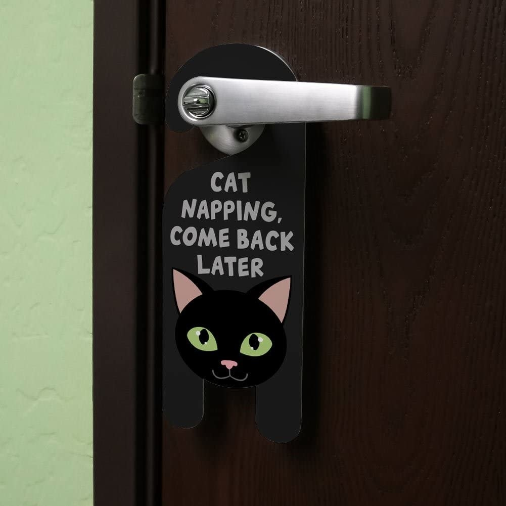 "A cat shaped door hanger that says ""Cat napping, come back later"""
