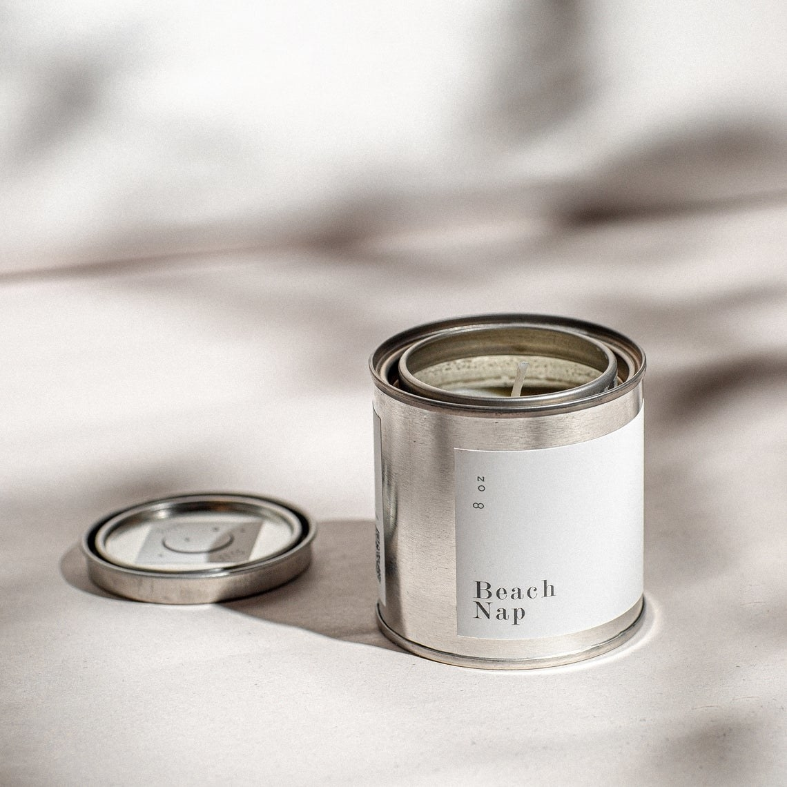 A product shot of the candle with a clean, minimalist label inside a tin container