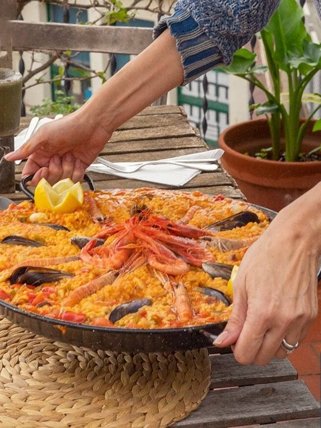huge pot of seafood paella being places on a table