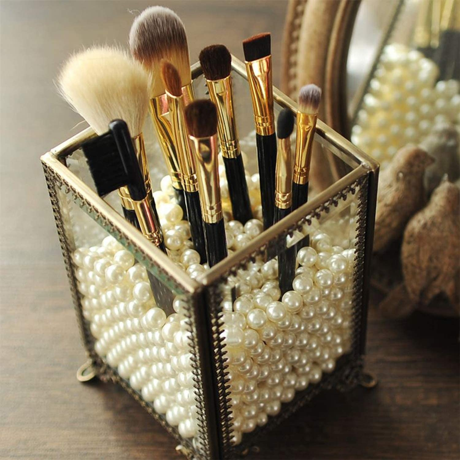 The vintage-inspired makeup brush holder filled with pearls and makeup brushes