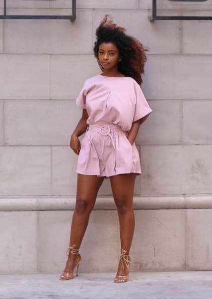 model wears blush colored short sleeve shirt and paperbag shorts