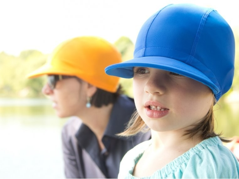 An adult wearing cap in yellow and a kid wearing one in green. The hat is like a baseball cap with a fit more like a swim cap