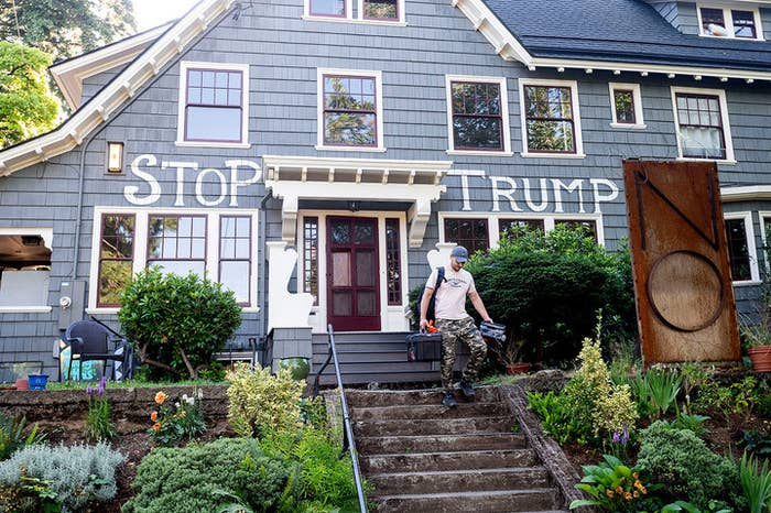 "Man walks down the stairs of a house with the words ""stop Trump"" painted on it."
