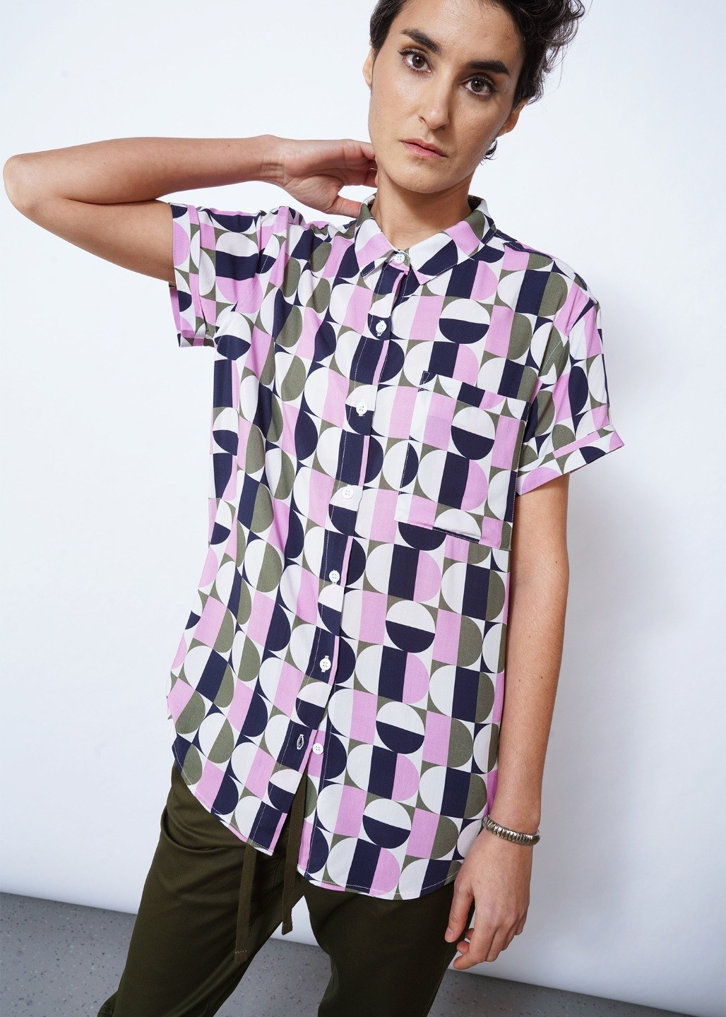 model wears geometric shirt with circles and squares