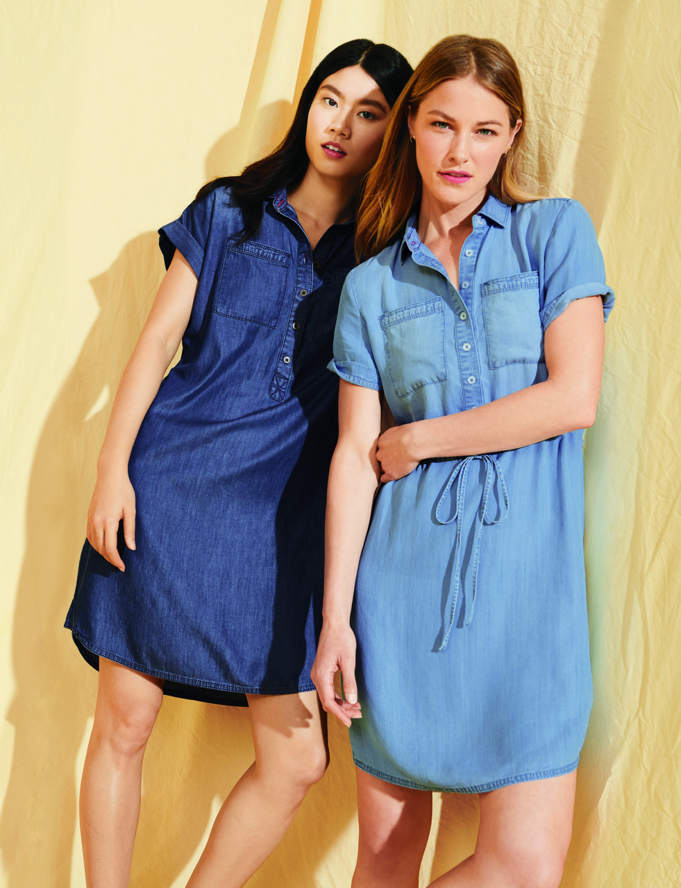 Two models wearing the dress in dark and light denim
