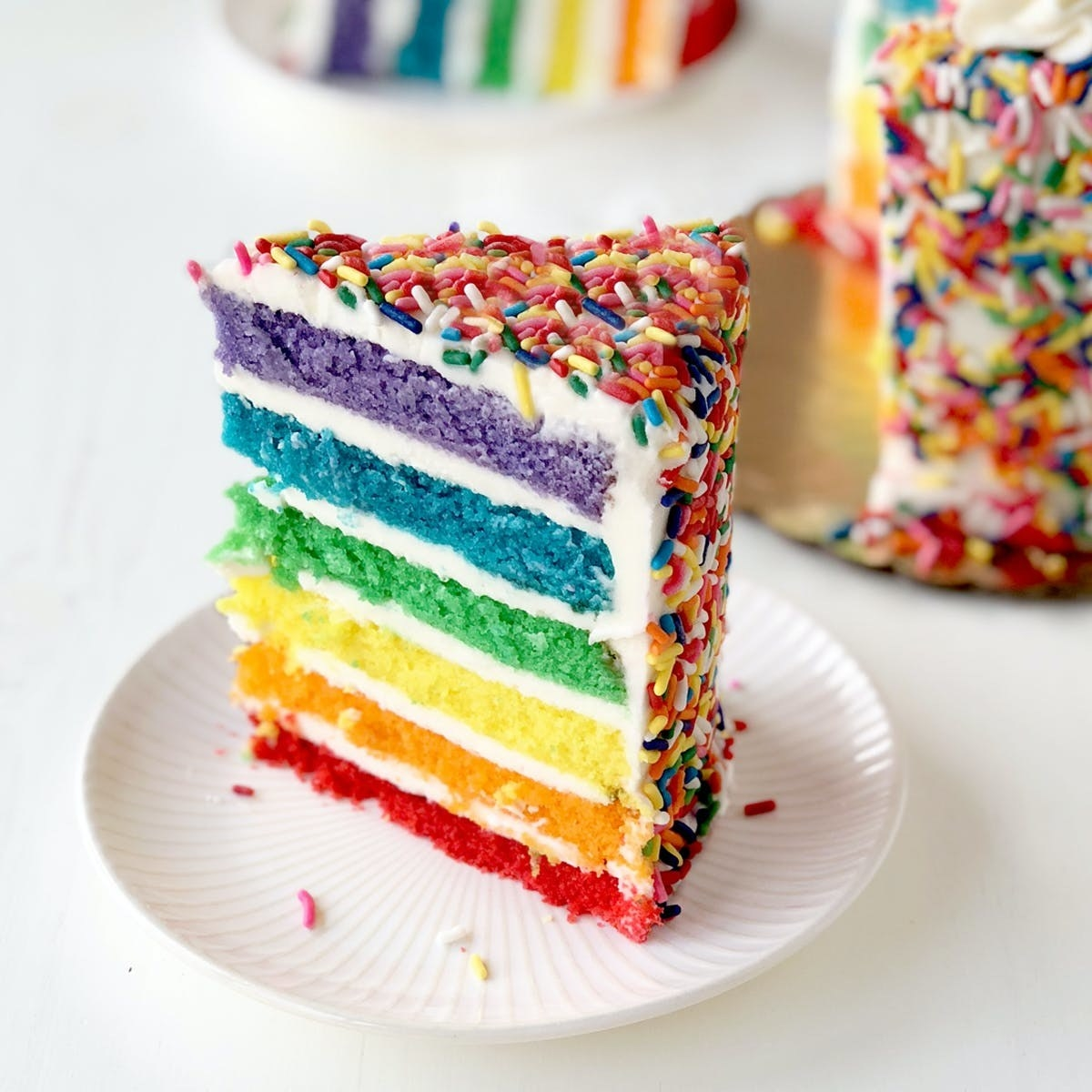 The cross section of the cake, which shows rainbow layers. The outside of the cake is covered with rainbow confetti