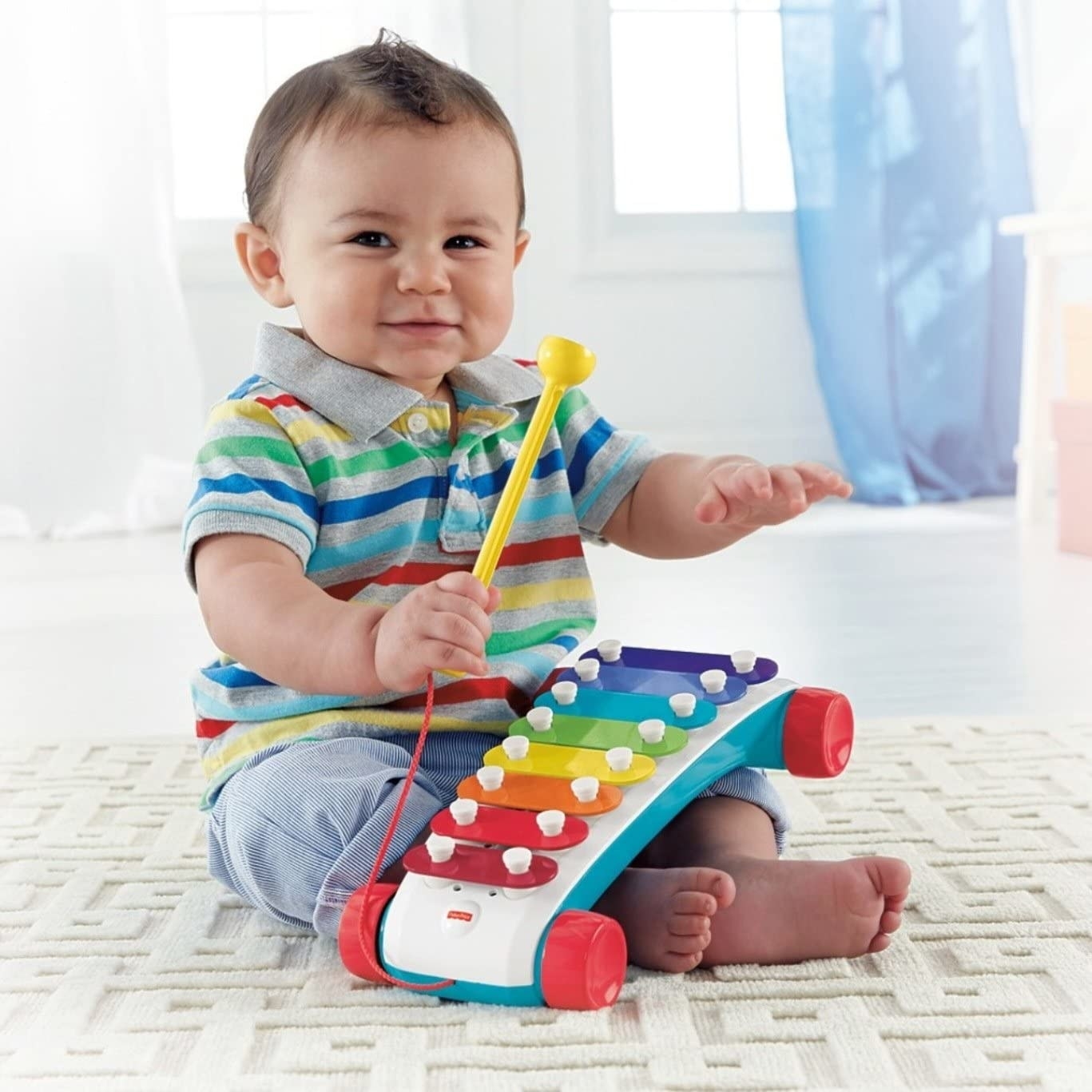 a child playing with a rainbow colored xylophone