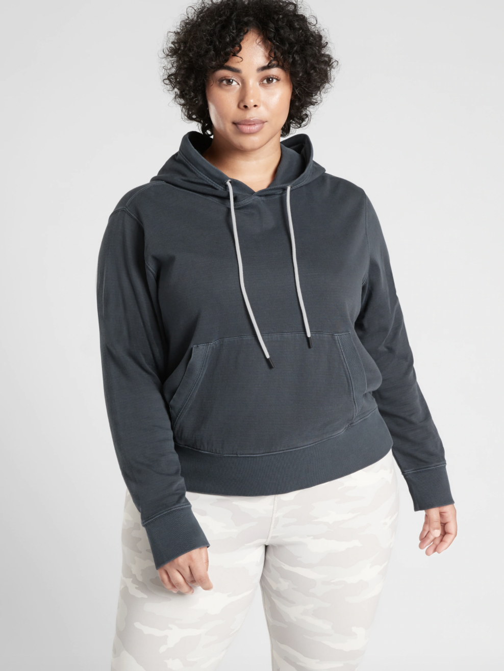 A model wearing a dark gray sweatshirt with a front pocket and drawstring hood