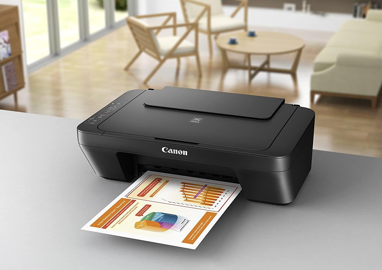 A printer on a desk printing a document